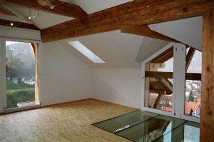 Altholzbalken kombiniert mit verputzten Decken und Wänden